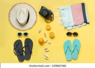Beach accessories for two, straw beach sunhat,towel, sun glasses on yellow with space for text. Summer concept.