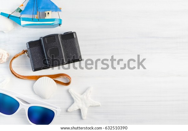 Beach accessories (White sunglasses,starfish,camera,boat,shell) on white plaster wood table top view,Summer vacation concept