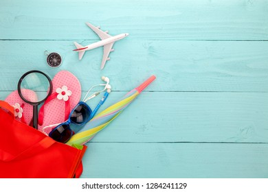 Beach accessory,hat,sunglasses,shoes,umbrella,airplane model,earphone,compass on blue wooden background, concept summer holiday travel background and summer sale.