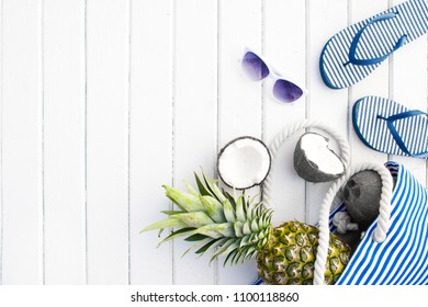Beach accessory,sunglasses,shoes, bag, coconut and pineapple on white wooden background, Concept summer holiday background and summer sale