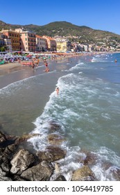 Beach at Alassio (ITALY) with people sunbathing, swimming and relaxing on a warm summer day. Alassio (SV), ITALY - August 21, 2017.