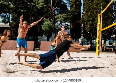 Beach amateur volleyball players in sunglasses and shorts jumping, standing in defense posture on the sandy court. Dynamic sport action near the net, outdoor.