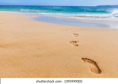 Beach background footprints in sand footprint closeup concept for travel vacation - footsteps in sand on summer tropical getaway holidays vacation with blue ocean . From Maui, Hawaii, USA.