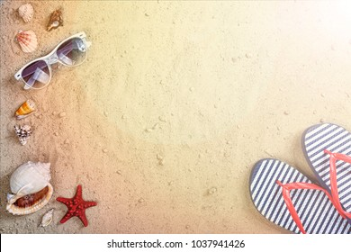 Beach background. Sunglasses, beach slippers and sea souvenirs on a sandy beach in the sun. Concept: summer vacation in warm countries, rest by the sea, summer time, travel
