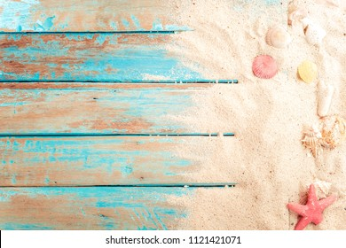 Beach background - top view of beach sand with shells, starfish on wood plank in blue sea paint color background. summer vacation concept. vintage color tone.