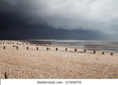 Beach in bad weather, coast with dark storm clouds. Winchelsea in england sussex with view of groyne wood pillars
