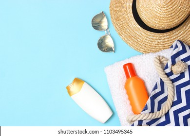 beach bag with beach accessories on a colored background top view. Sunscreen, towel, glasses, hat.