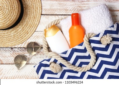 beach bag with beach accessories on a wooden background top view. Beach bag, towel, sunscreen, glasses, hat.