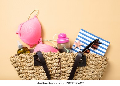 Beach bag with elegant women accessories on yellow background. Top view beach bag with swimsuit, water bottle, essential oil, book, sunglasses. Flat lay stuff. Summer fashion, holiday vacation concept
