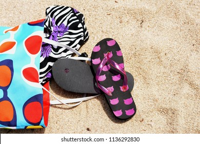 Beach bag with flip flops on the sand. Summer holiday background
