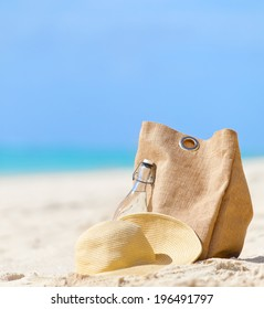 beach bag, straw hat and bottle of water at the beach, vacation concept