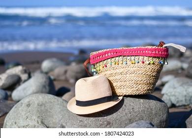 Beach bag and sun hat on the stony beach