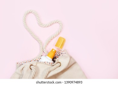 beach bag with beach top view with sunscreen on pastel pink background. Horizontal image