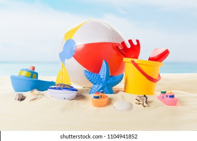 Beach ball and bucket with toys in sand on blue sky background