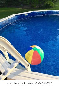 A beach ball floats on the water in an above-ground swimming pool on a sunny summer's day.