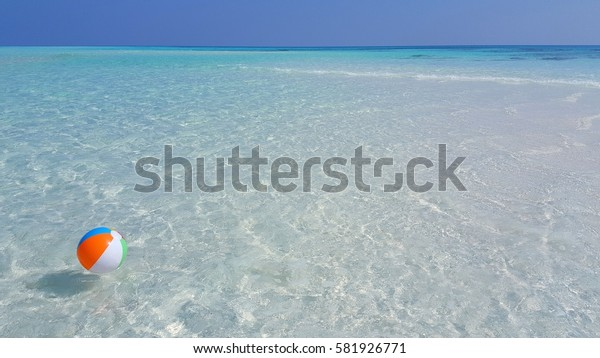 Beach ball on the blue turquoise lagoon sea water with blue sky background