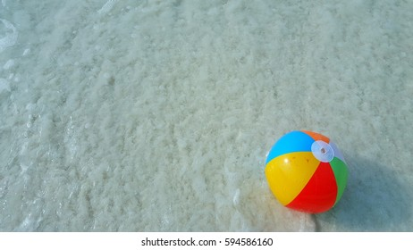 Beach ball on the clear sea water background summer holiday vacation