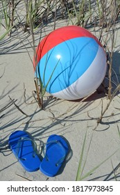 Beach ball and a pair of blue flip flops sitting in the sand at the beach.