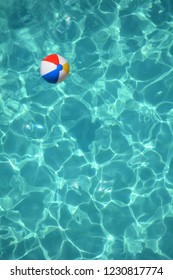 Beach ball in a refreshing blue swimming pool.