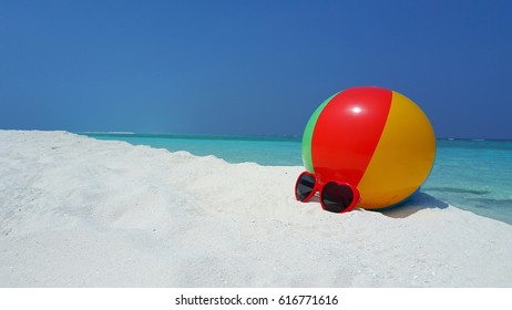 Beach ball and sunglasses on the white sand