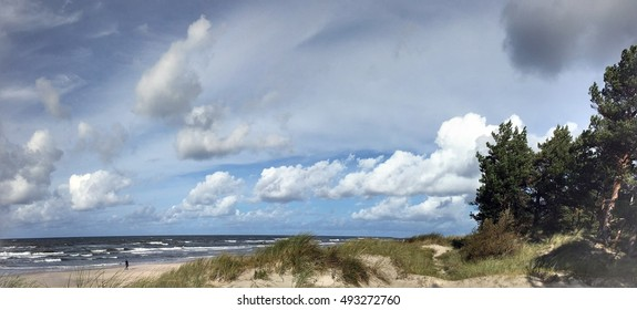 Beach of Baltic Sea in Palanga, Lithuania on a sunny autumn day: Pines, Sand, Waves, Clouds