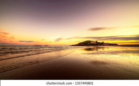 The beach at Bantham during sunset in South Devon, with Burgh island in the background