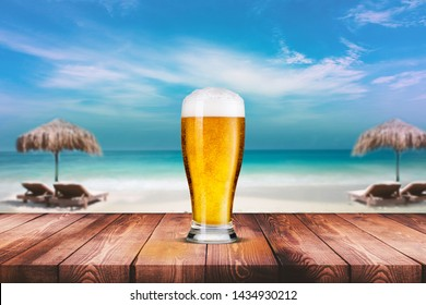 Beach bar and beer. Blurred background of beach bar at summer time. Beach and wood table composition.