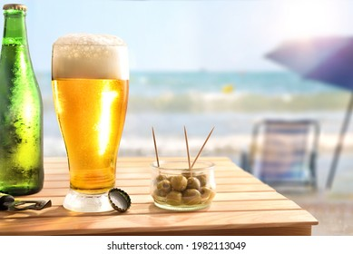 Beach bar concept with wooden table with beer and olives to nibble with beach in the background with umbrella and chair.