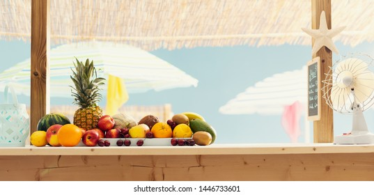 Beach bar kiosk with delicious fresh fruit on the counter and colorful umbrellas in the background, summertime concept