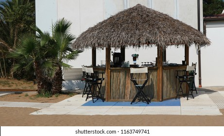 Beach bar with thatched roof, wood and bamboo walls, chairs, beer and glasses. No people, background