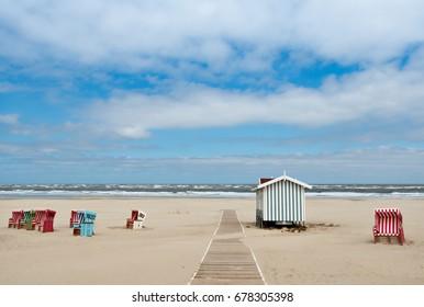 Beach baskets on a sandy beach with blue sky, on the island of Langeoog
