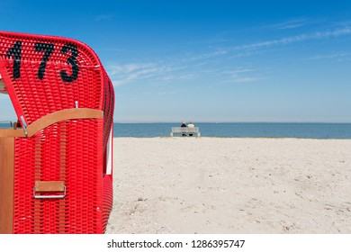 Beach baskets on a sandy beach and a couple on a bench with blue sky, on the island of Langeoog