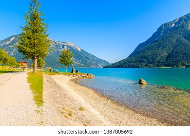 Beach at beautiful Achensee lake on sunny summer day with blue sky, Karwendel mountain range, Tyrol, Austria