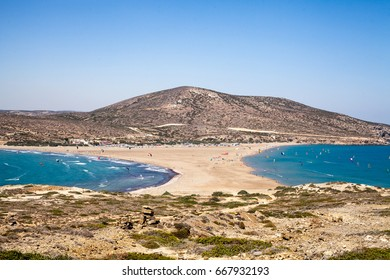 Beach between two seas. Beach between the islands of Rhodes and Prasonisi. Road across the sea. People practicing Kitesurfing. Colorful kites on the sea shore. Blue waves sea and sky.