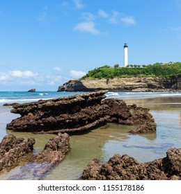 Beach in Biarritz city at low tide with rocks on the sand and the lighthouse in the background. Basque country of France.