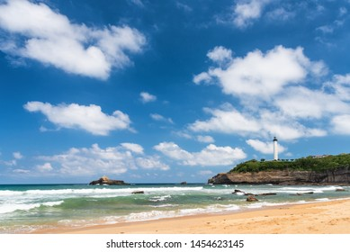 Beach of Biarritz city with waves and polarized white clouds in the sky. Basque coast of France.