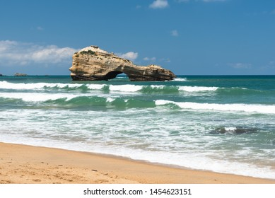 Beach of Biarritz city with waves and a rock. Basque coast of France.