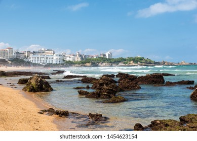Beach of Biarritz city with waves and rocks on the sand. Basque coast of France.