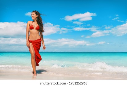 Beach bikini model in red swimsuit and skirt for wellness spa luxury. Hair removal laser treatment for legs and body summer ready vacation Asian woman walking relaxing at Caribbean travel holiday.