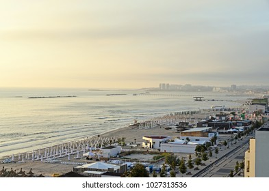 Beach of Black Sea from Mamaia, Romania with golden sands, sun umbrellas, sunbeds, blue clear water, bars and hotels.