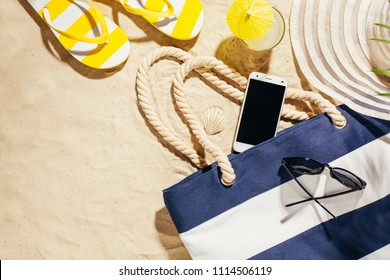 Beach blue bag, flip flops and cell phone on a tropical beach. Top view with copy space.