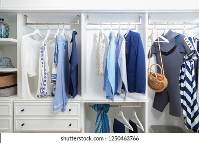 beach blue clothes and windsurf suit hanging in white wardrobe in home