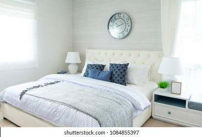 beach blue pillow on bed with side table lamp and large clock on wall in bedroom