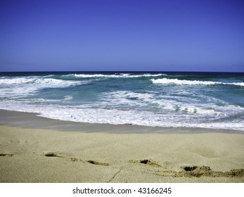 Beach with blue waters and foot print in the sand.