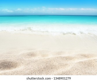 Beach blurred background. Tropical island paradise. Sandy shore washing by the wave. Bright turquoise ocean water. Dreams summer vacations destination. Crystal clear sea.