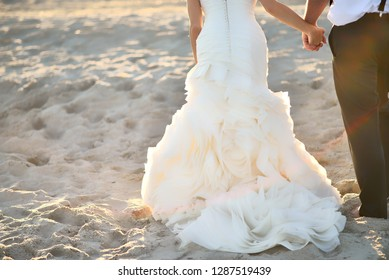 Beach Bride and Groom from waist down walking hand in hand off center right walking away from camera towards sunset with natural sunflare