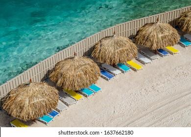 Beach cabanas and sun loungers on a beach in Aruba