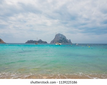 Beach, Cala D'hort, in Ibiza, Spain. Islotes de Es Vedrá and Es Vedranell and pleasure boats