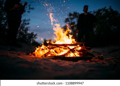 Beach campfire with people in the background and sparks flying around