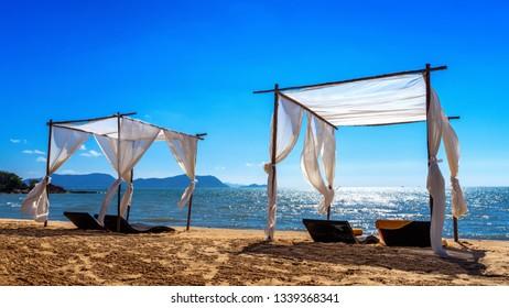 Beach canopies with sun loungers on beach.